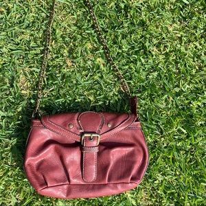 Small rustic red clutch handbag with gold chain.